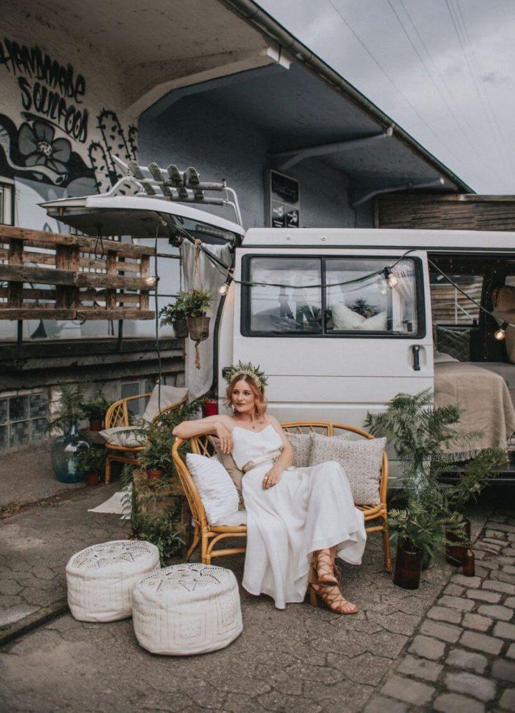 Braut vor Hochzeitsbus